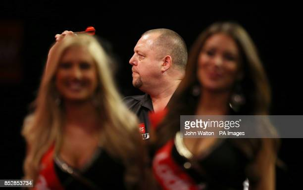 Mervyn King practices before the start of his match against Ricky Evans as the oche girls walk off stage during day eleven of The Ladbrokes World...