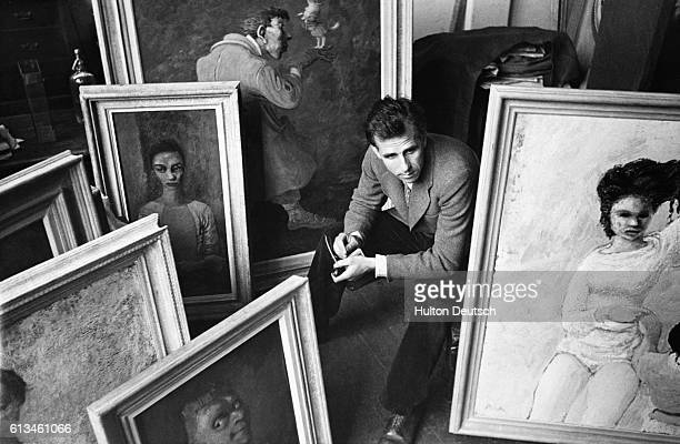 Mervyn Laurence Peake the English author and artist sits amidst a collection of oil paintings His books include Mr Pye and Titus Alone