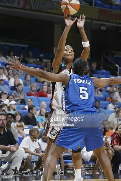 Mery Andrade of the Cleveland Rockers passes up over Elaine Powell of the Orlando Miracle in the game on June 19 2002 at Gund Arena in Cleveland Ohio...