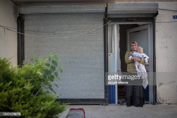 Meryem from Aleppo and her baby is seen at the door of the small store where they live together in Gazikent Gaziantep Turkey on 22/4/16 Tens of...