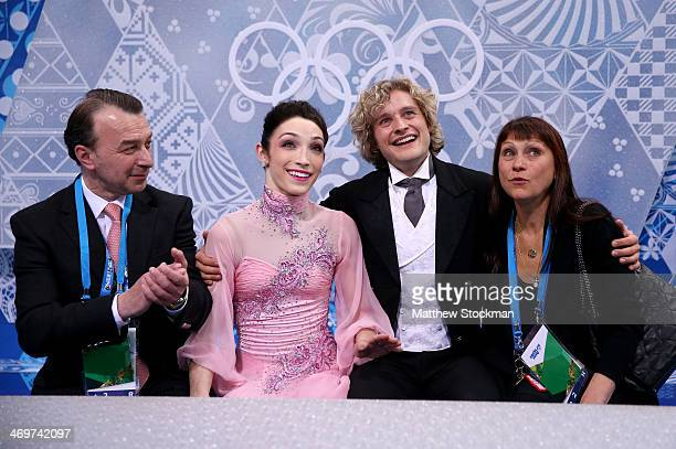 Meryl Davis and Charlie White of the United States wait for their score with their coaches Oleg Epstein and Marina Zoueva after competing during the...