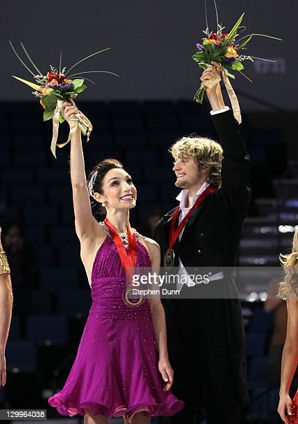 Meryl Davis and Charlie White wavew on the awards podium after winning the gold medal in the ice dance competition during Hilton HHonors Skate...