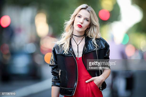 Meryl Denis is wearing a Dezzal red suit and a Dezzal black jacket during a street style session in the 8th quarter of Paris on July 19 2016 in Paris...