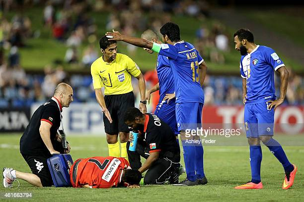 Mesaed Alenzi of Kuwait reacts to Mohamed Ali Siyabi laying on the ground injured during the 2015 Asian Cup match between Oman and Kuwait at Hunter...