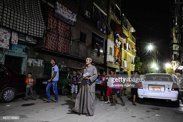 A mesaharati beats his drum which is under a plastic container in Ramadan month and awakens people for suhoor by shouting their name in Cairo Egypt...