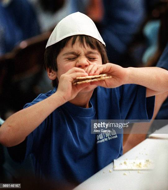 MEseder0415AAG––Tal Meltzer of Irvine has difficulty biting through his matzoh sandwich during a practice Passover Seder for day school children at...