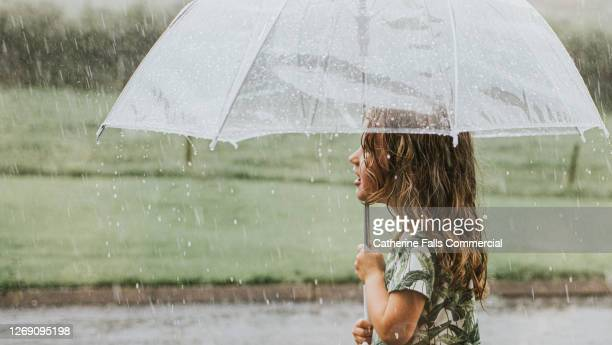 mesmerised little girl holds a transparent umbrella in a heavy rainstorm - awe stock pictures, royalty-free photos & images