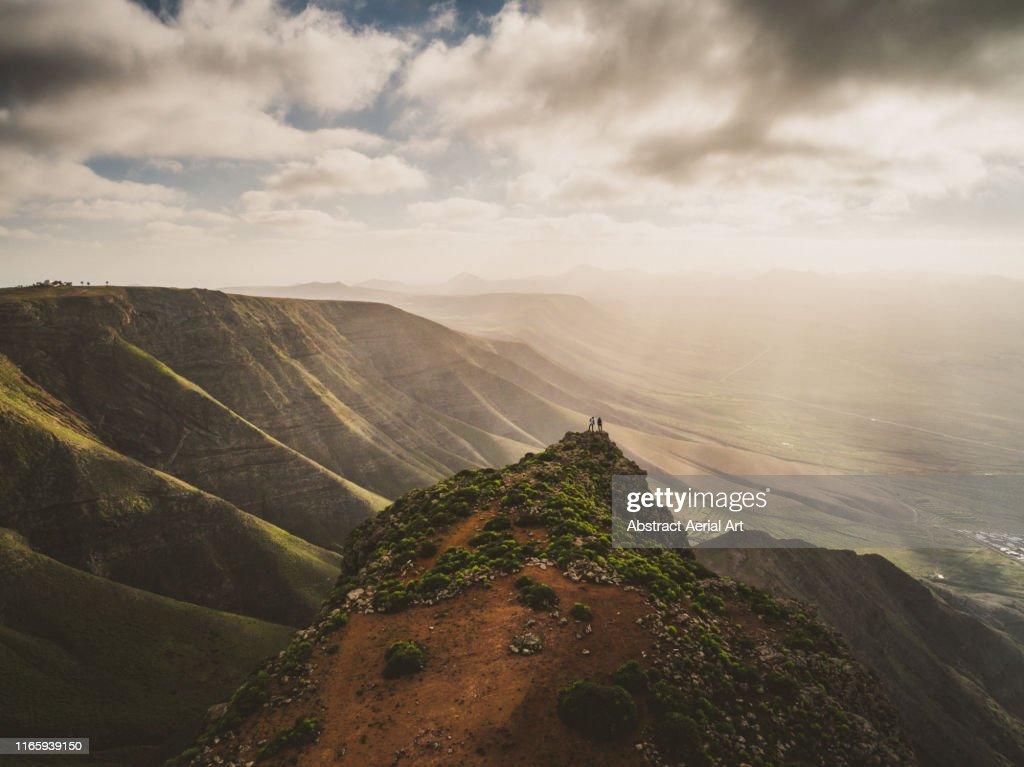 Mesmerising views enjoyed by two hikers at sunset, Lanzarote : Foto de stock