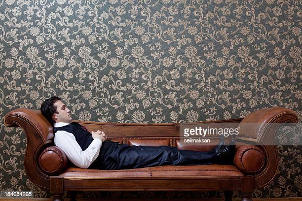 mesmerized man lying down on coach in psychiatrist office - psychiatrist's couch stock pictures, royalty-free photos & images
