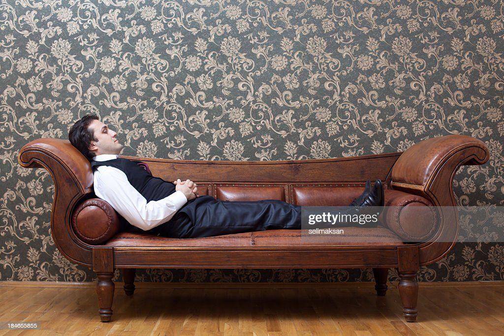 Mesmerized man lying down on coach in psychiatrist office : Stock Photo