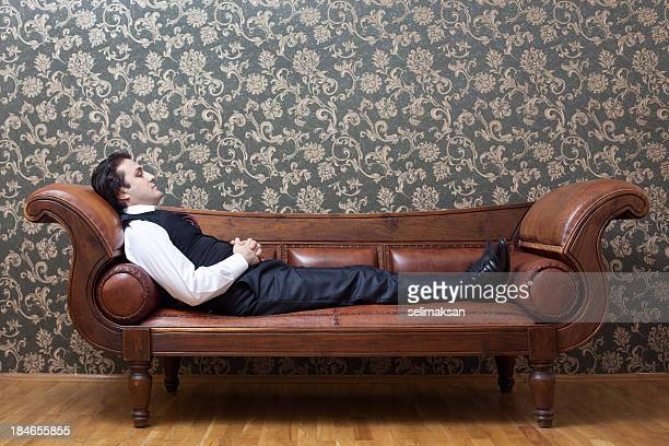 Mesmerized man lying down on coach in psychiatrist office