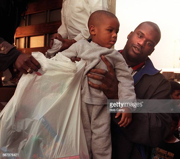 MESnow#11223BCb–––Laker star Shaquille O'Neal gives Duveet Smith a lift after Smith picked up Christmas presents at the Watts Labor Community Action...