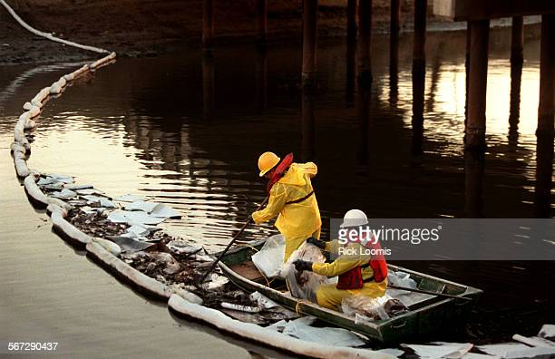 MEspillboat1213RL––Foss Environmental In Infrastructure spill technicians Roger Noriega and Ignacio Cuevas work to contain an oil spill with an...