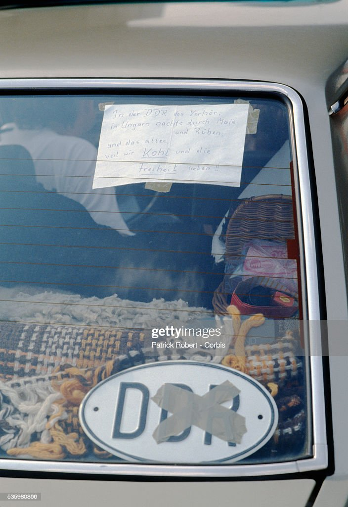 A message and anti-DDR (German Democratic Republic) sign sit in the rear window of the car of an East German at the border of Hungary and Austria. Egon Krenz replaced East German leader Erich Honecker, causing many East Germans to flee the country. Thousands more poured into West Germany with the fall of the Berlin Wall.   Location: Border of Hungary and Austria.