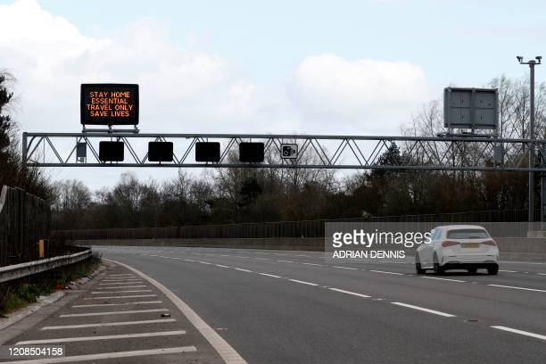A message asking people not to travel is dislayed as a car travels along the almost deserted M3 motorway near Fleet south west of London on March 29...