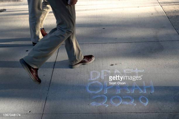 Message calling for Oprah Winfrey to run for president is chalked on the sidewalk outside of a security fence that surrounds the Wisconsin Center...