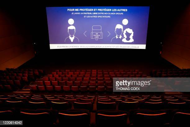A message concerning the distance measures is displayed on a giant screen inside a movie theatre room in Paris on June 17 few days before all the...
