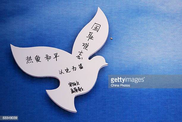 A message from a visitor that says Love peace never forget the shame of our nation take history as a mirror is written on a paper dove at an...