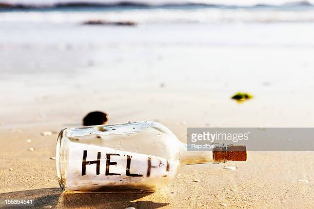 message in a bottle on beach: help! - stranded stock photos and pictures