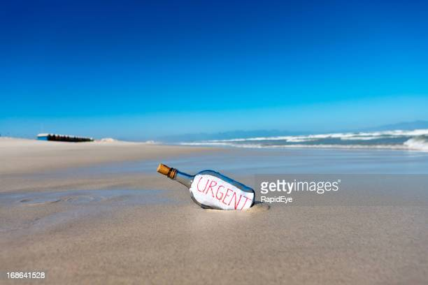 Message in bottle on deserted beach says Urgent
