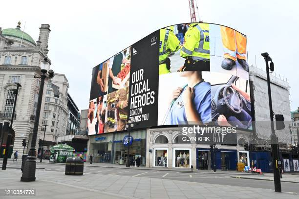 A message in tribute to all those workers providing essential services during the coronavirus pandemic is seen on the giant billboard in Piccadilly...
