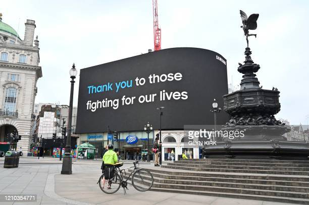 A message in tribute to NHS staff is seen on the giant billboard in Piccadilly Square central London on April 18 2020 during the novel coronavirus...
