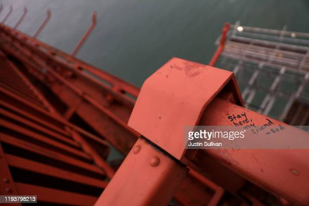 A message is seen on the Golden Gate Bridge near where the new suicide prevention net is being installed on December 13 2019 in San Francisco...