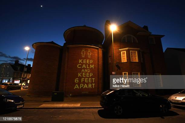 A message of 'Keep Calm And Keep 6 Feet Apart' by Illustrator and artist Mike Dicks is projected onto a wall of a church on March 29 2020 in Brighton...