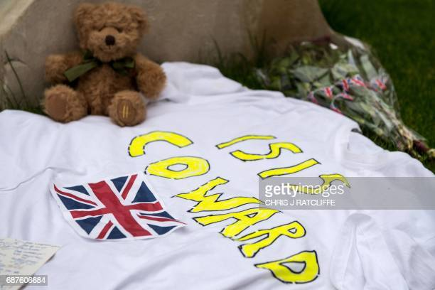 A message reading 'ISIS Coward' is pictured alongside a teddy bear and flowers in Albert Square in Manchester northwest England on May 24 as tributes...