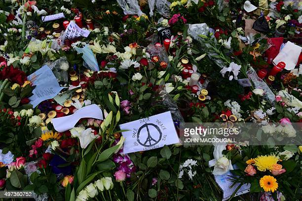 A message reads ' Peace ' in several languages around the #PeaceForParis logo created by French graphic designer Jean Jullien amount flowers and...