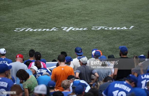 A message thanking fans appears on the artificial turf on the final game of the regular season during the Toronto Blue Jays delivers a pitch in the...