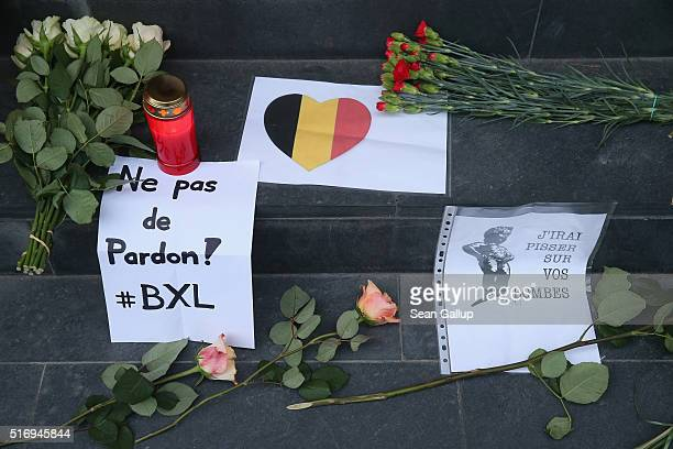 Messages left by mourners including a heart with the colors of the Belgian flag a message in French that reads 'No Forgiveness' and another one that...