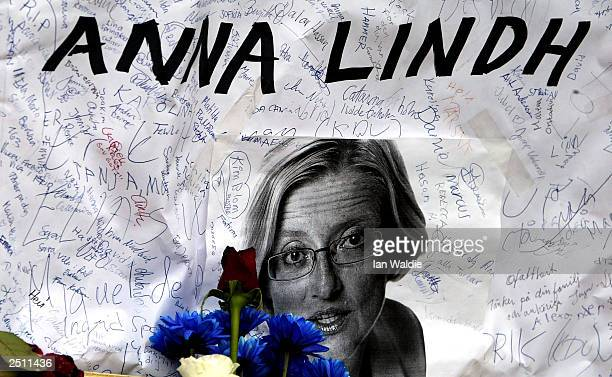 Messages of condolence are written on a poster carrying a picture of murdered Swedish Foreign Minister Anna Lindh at Karolinska Hospital where she...