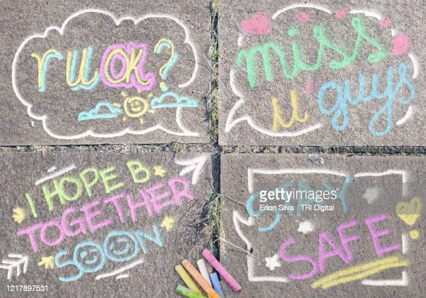 messages of hope and affection drawn on the floor giving optimism to people in social confinement during the quarantine caused by covid-19 - corona sun stock pictures, royalty-free photos & images