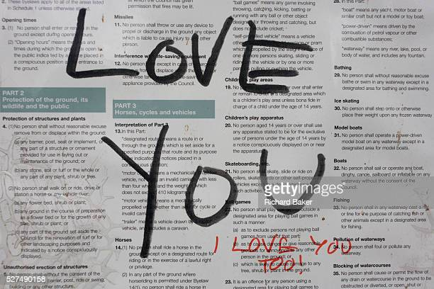 Messages of love written in marker pen on a public park sign containing local bylaws The large letters form the words LOVE YOU in the centre of frame...