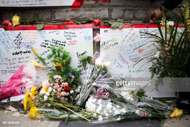 Messages written in different languages can be seen through flowers strewn on a memorial for victims of yesterday's crash on Yonge St at Finch Ave on...