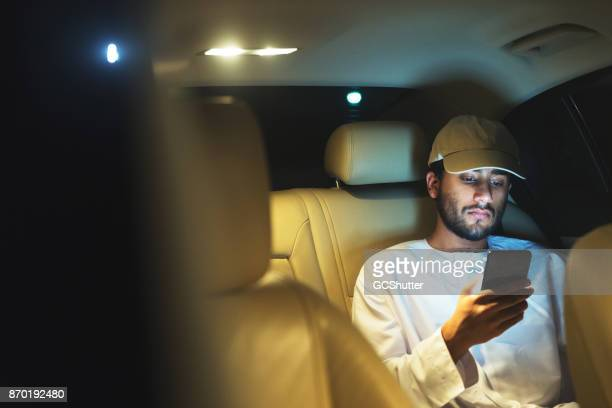 Messaging his friends from the backseat of the car