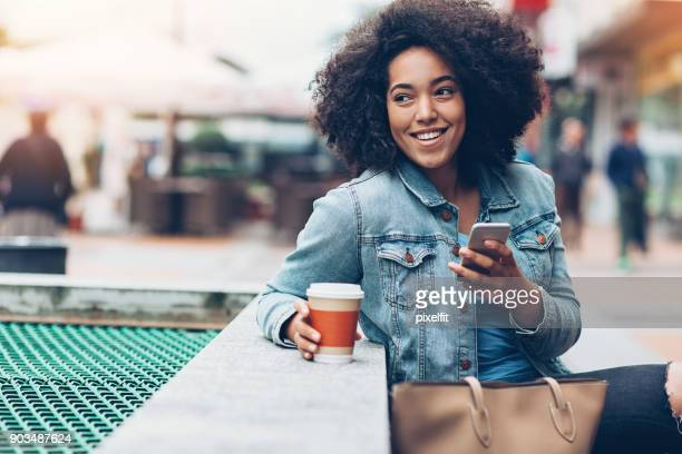 messaging outdoors in the city - mixed race person stock pictures, royalty-free photos & images