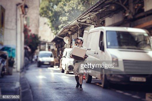 Sac coursier, livraison de colis, marchant dans la rue à côté de sa FOURGONNETTE