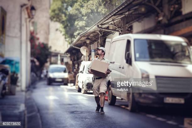 Mensajero de entrega paquete, caminar en la calle Al lado de su van