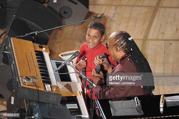 Messenger of Peace Stevie Wonder gives a harmonica to a blind boy during the United Nations Day Concert at United Nations on October 24 2012 in New...