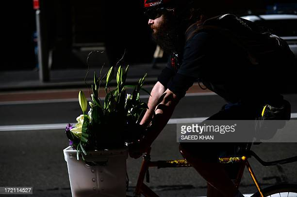 A messenger powers his bike to deliver a flower bouquet in the central business district of Sydney on July 2 2013 Australia's central bank held the...