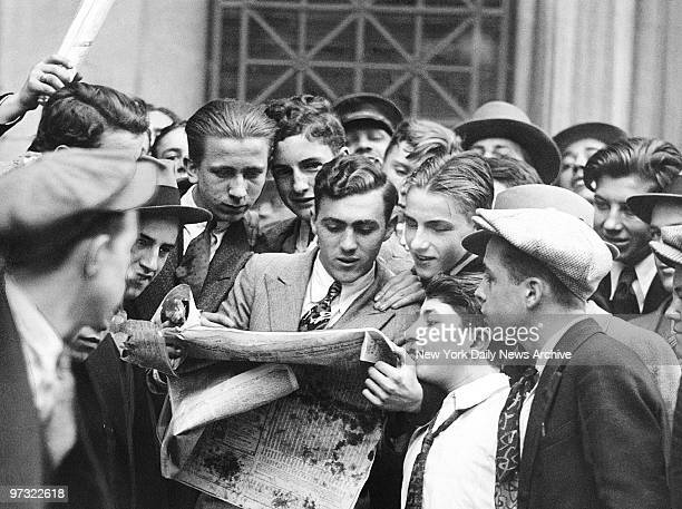 Messengers from brokerage houses seem unconcerned as they crowd around a hardtoobtain newspaper after the first Wall Street stock market crash on...