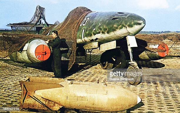 A Messerschmidt ME 262 V7 jet fighter is serviced by German personnel It is partly under a camouflage net 1945 A Bomb is sitting on the ground near...