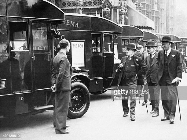 Messieurs Ramsey MacDonald Stanley Baldwin et Sir John Simon discutant avec le chauffeur avant de rentrer dans le cinema mobile le 13 juin 1934 a...