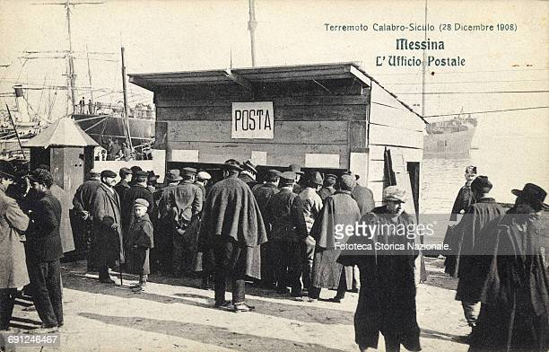 the post office temporarily housed in a wooden shack a small crowd of earthquake victims flock to send or receive news of their loved ones the era of...