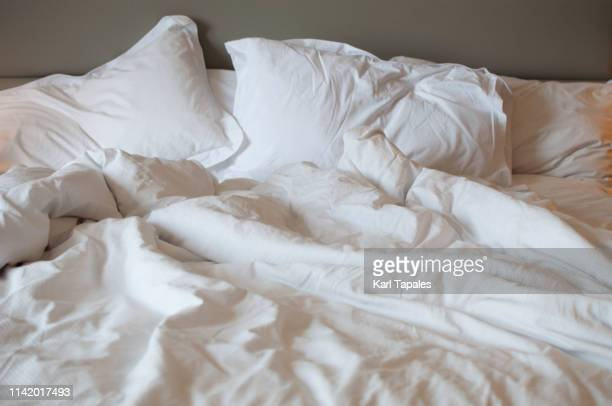 a messy bed with comforter and pillows - sex stock photos and pictures