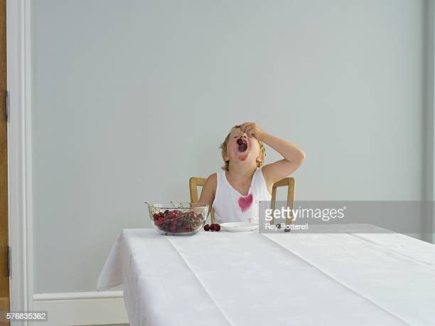 Messy Boy Eating Cherries at Table