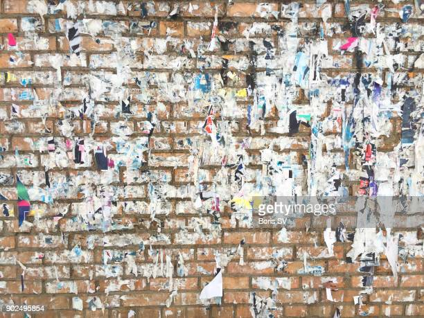 Messy brick wall with torn remains of paper posters