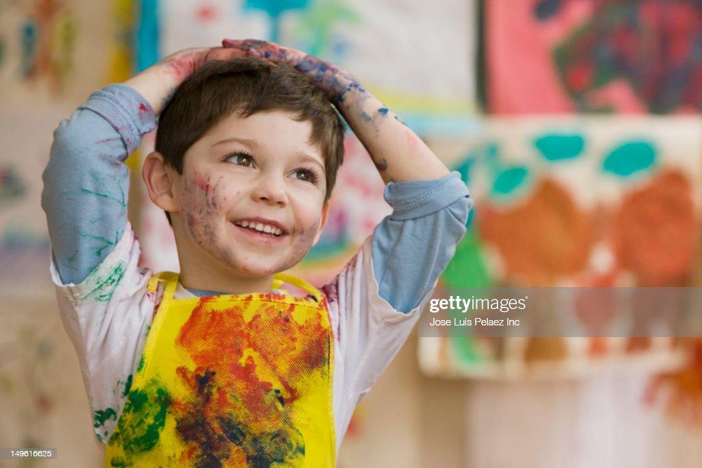 Messy Caucasian boy in art class : Stock Photo